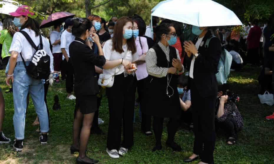 People wait in groups to undergo coronavirus tests in Beijing.
