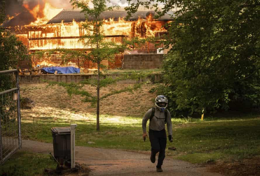 Ein Mann geht schnell, nachdem er in Nevada County, Kalifornien, ein Haus überprüft hat, das bei einem Feuer in einem Fluss brennt.