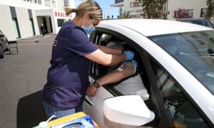 Medical personnel giving Covid jabs to drivers in the first drive-through vaccination centre in France.