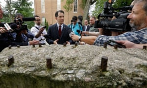 Republican presidential candidate Scott Walker speaks to reporters in front of a piece of the Berlin Wall in the Ronald Reagan Peace Garden at Eureka College, Illinois, on Thursday.