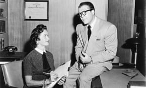 George Reeves, as Clark Kent, sits on desk beside Noel Neill, as Lois Lane, in a still from the television series, Adventures of Superman.