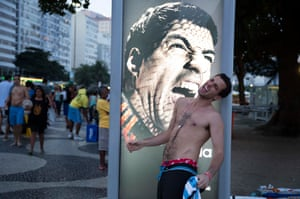 A fan getting their photo taken pretending to be bitten by Suárez at Copacabana beach during the tournament.
