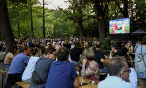 People at Berlin's Cafe am Neuen See beer garden, enjoy a drink in the sunshine as Burak Yilmaz and Giorgio Chiellini shake hands.