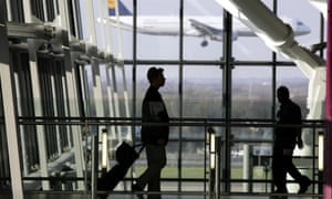 Passengers walk past the windows of a departure lounge as a plane lands outside.