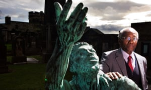 Professor Geoff Palmer, standing beside a statue of a freed slave in the Calton cemetery, Edinburgh, welcomed the report.