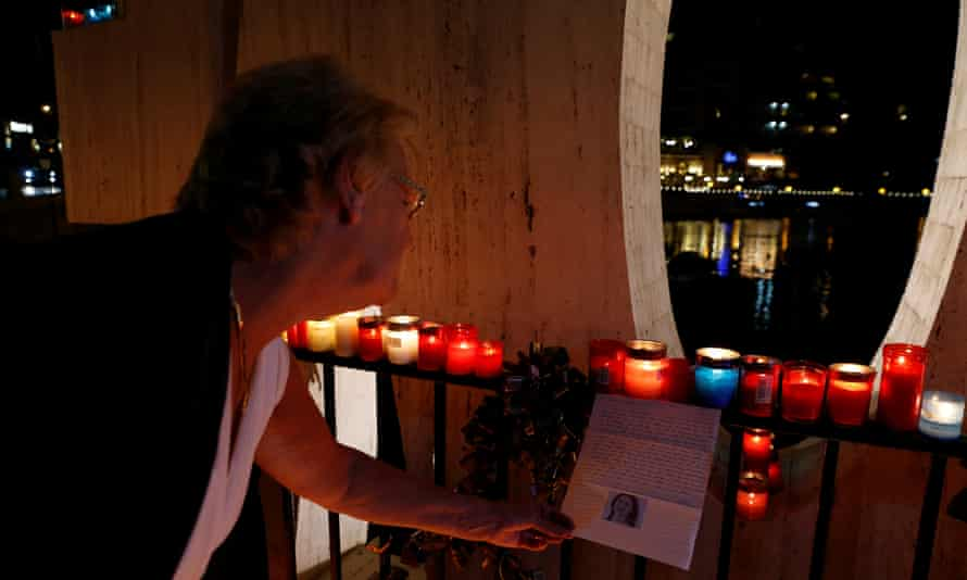 A woman reads a letter to investigative journalist Daphne Caruana Galizia during a silent candlelight vigil to protest against her murder, in St Julian's, Malta.
