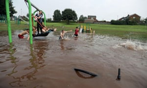 Children playing in a flooded park in Newcastle-under-Lyme.