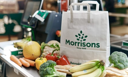 Morrisons' new paper grocery bags, priced at 20p, surrounded by fruit and vegetables.