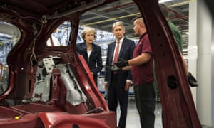 Theresa May and chancellor Philip Hammond at a production line during a visit to the Jaguar Land Rover factory in Solihull.
