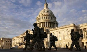 National Guard members walk in front of the US Capitol on Thursday, after the House voted to impeach Donald Trump in Washington DC Wednesday evening.