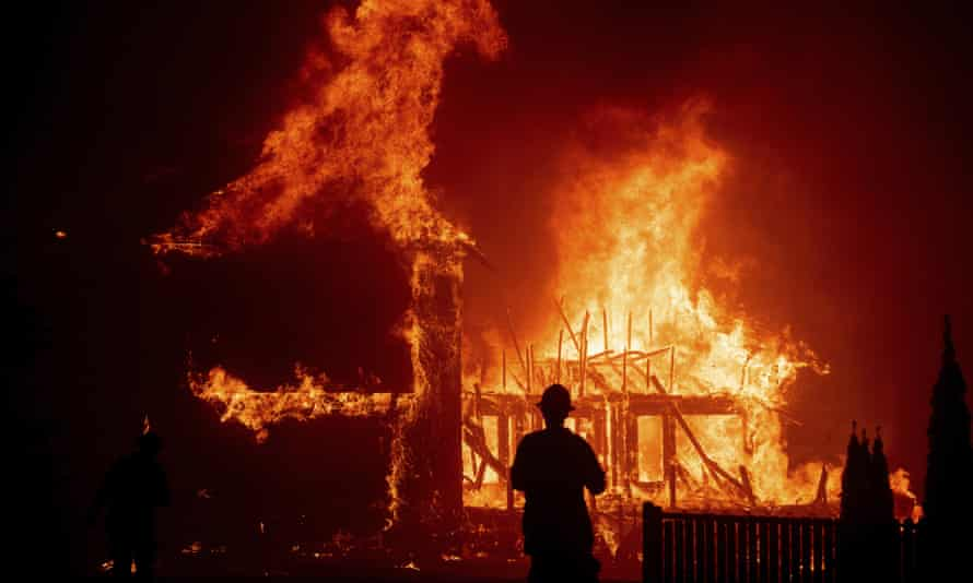 A home burns as the Camp fire rages through Paradise, California, 9 November. PG&E is facing billions of dollars in liabilities over 2018 wildfires.