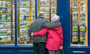 Older couple looking in estate agent's window