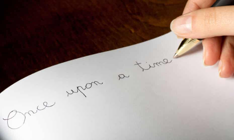 """Person writing """"once upon a time"""" by hand in a book."""