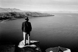 man on rock overlooking Lake Titicaca