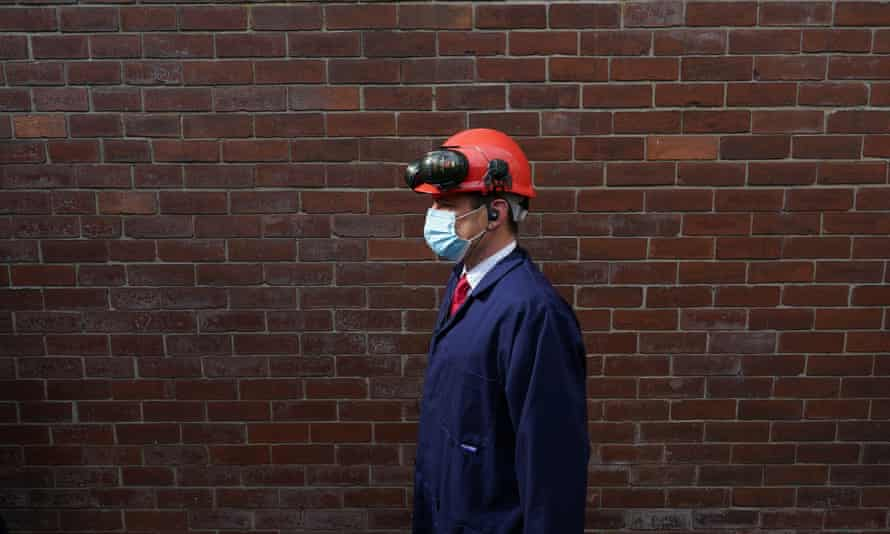 Paul Williams on a visit to an industrial site, wearing a hard hat, goggles and mask, photographed in profile against a brick wall