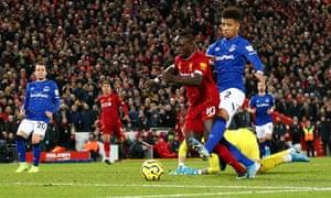 Liverpool's Sadio Mane is challenged by Everton's Mason Holgate.