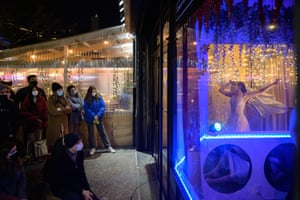 people watch a stage show in a shop window