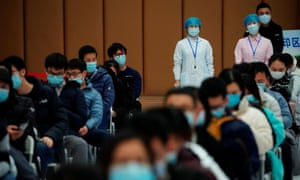 People sit at a vaccination site after receiving the Covid vaccine in Shanghai, China.