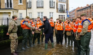 David Cameron greets British soldiers working on flood relief after the river Ouse burst its banks in York on 28 December.