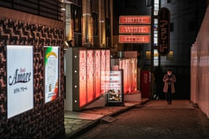 A man wearing a face mask checks his phone as he walks past a love hotel in Love Hotel Hill, Tokyo