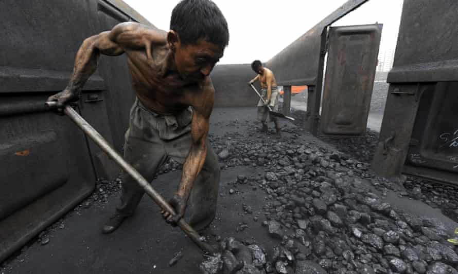 Workers unloading coal at a storage site along a railway station in Hefei, China. <br>