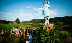People gather around a statue of Melania Trump on the outskirts of Sevnica, on 5 July.
