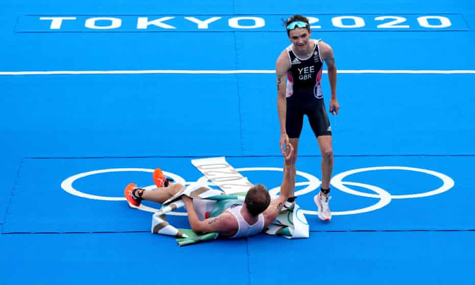 Norway's Kristian Blummenfelt celebrates winning the men's triathlon with Great Britain's Alex Yee (standing), who finished second
