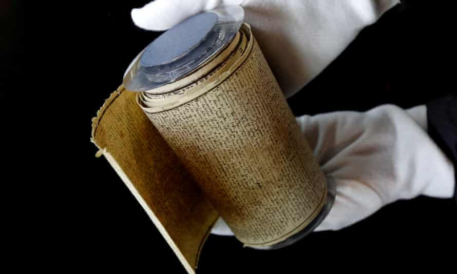 An employee displays the Marquis de Sade's original rolled manuscript for The 120 Days of Sodom, before its auction in Paris in 2017.