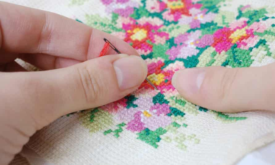 Woman's hands over cross-stitch embroidery