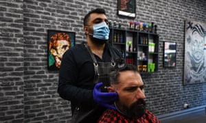 Barber Ethan Hemtyar gives client Carlo Greco a hair cut at Captain Style Barbershop in Melbourne, Monday 19 October 2020.