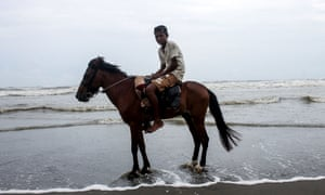 A youth rides a horse while he waits for customers along a beach in Cox's Bazar on June 16, 2021, as activists warned that such horses used for tourist rides were dying with their owners unable to feed them due to a lack of income.