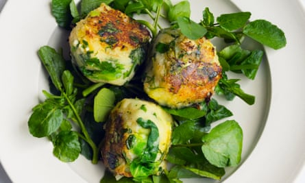 three round patties of bubble and squeak on salad leaves on a plate