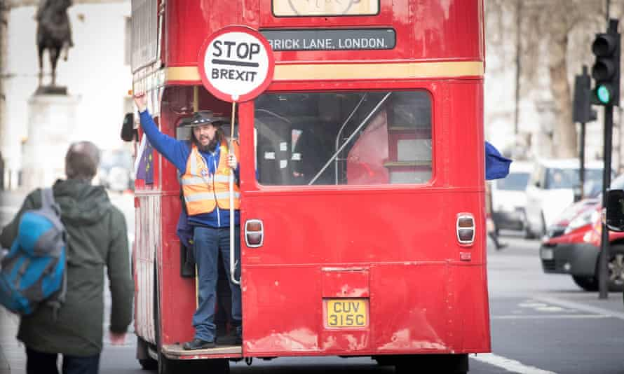 A man holds a 'Stop Brexit' sign aboard a double-decker campaign bus travelling down Whitehall in Westminster, London