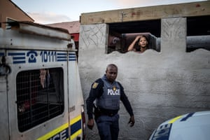 The relative of a man detained in a police van looks on as a South African policeman leaves their residence during a joint police operation in the Mitchel's Plan district of the Cape Flat, Cape Town.