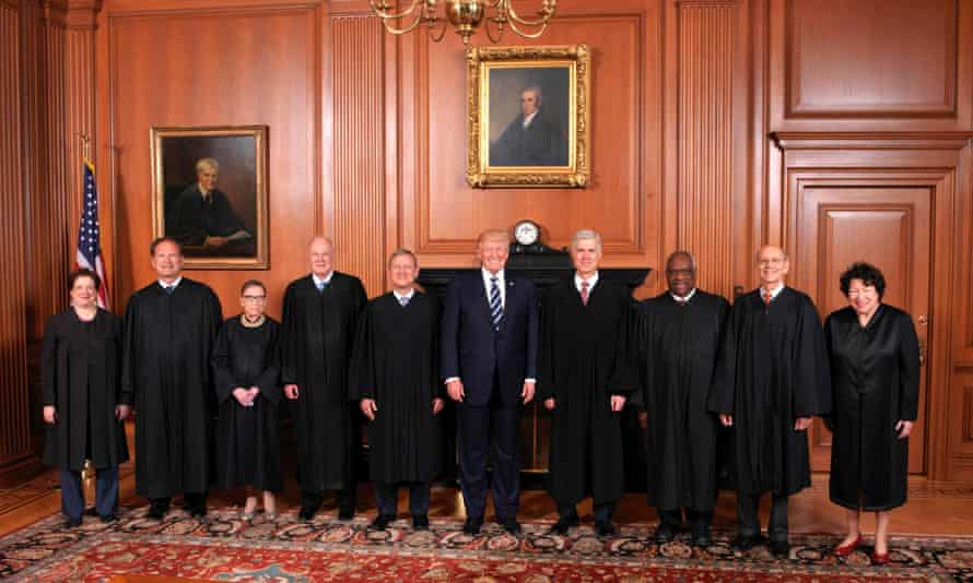 Justice Neil Gorsuch stands fourth from right, next to Donald Trump, as the members of the supreme court pose with the president in Washington.