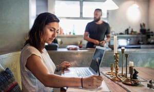 woman uses laptop at home with man in background