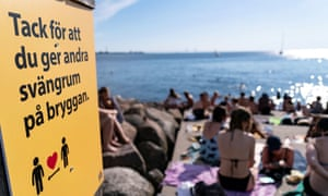 An information sign recommends people to keep social distance due to Covid-19 pandemic, where people sunbathe and swim at a bathing jetty in Malmo, Sweden.