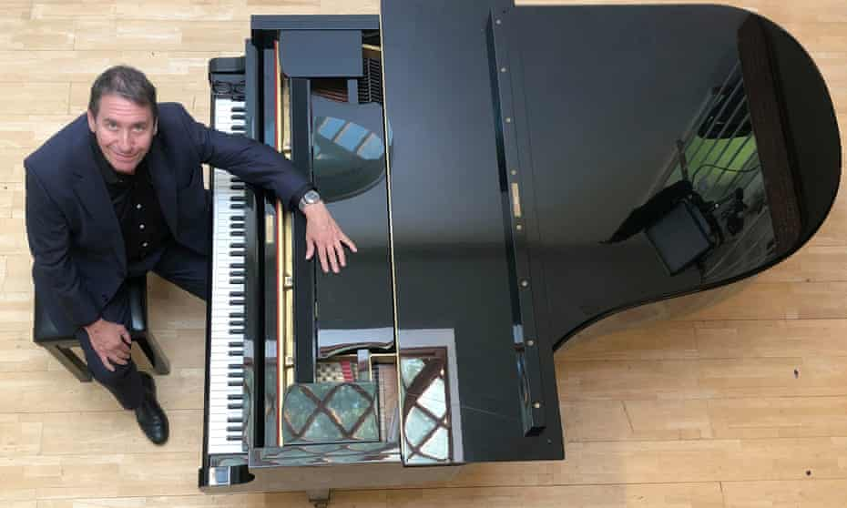 Jools Holland sitting at a grand piano, photographed from above