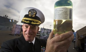 With guided missile destroyer USS Stockdale in the background, Capt Brian Weiss holds a sample of the biofuel blend.