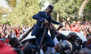 Bobi Wine is helped down from the top of a car on Thursday after he addressed a crowd outside his home in Kampala.