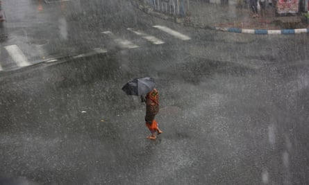 A woman tries to manage her umbrella between storm with heavy rain on street in Calcutta, eastern India, 23 May 2016.