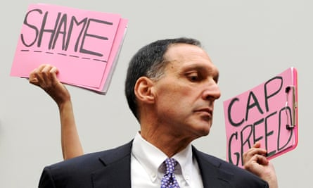 Protesters hold signs behind Lehman Brothers CEO Richard Fuld.