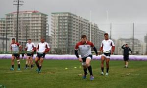 Elliot Daly strides away from Anthony Watson in England training at Arcs Urayasu Park.