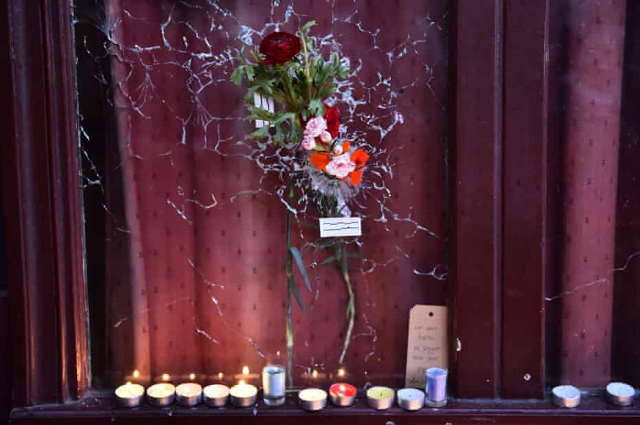 """Candles have been lit next to a flower"""" hanging on a broken window of """"Le carillon"""" restaurant one of the site of the attacks in Paris on November 15, 2015"""