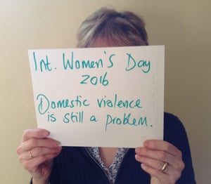 Woman holding sign saying domestic violence is still a problem.