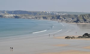 People walk on Tolcarne beach in Newquay, Cornwall