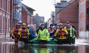 Members of rescue services and armed forces help evacuated people from the centre of York on 27 December 2015.