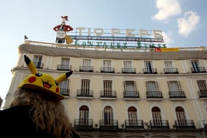 A girl wears a cap depicting Pokémon character Pikachu, at Puerta del Sol square.