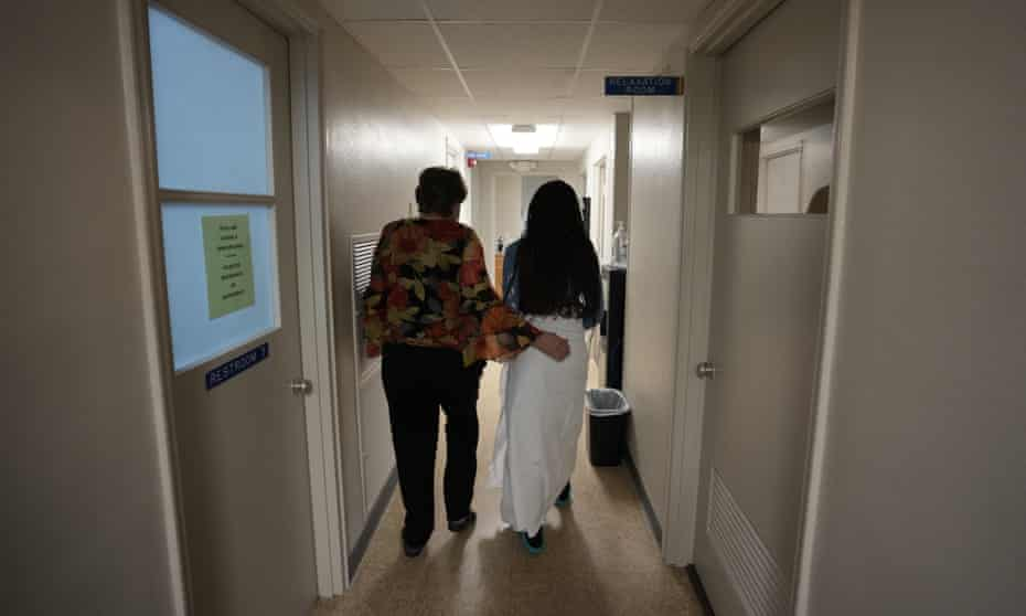A 33-year-old mother of three from central Texas is escorted down the hall by clinic administrator Kathaleen Pittman prior to getting an abortion, Saturday in Shreveport, Louisiana.