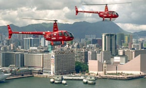 Two red helicopters fly over Hong Kong